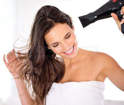 Buy stock photo A beautiful woman smiling while drying her hair with a hairdryer