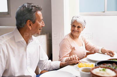 Buy stock photo Shot of a senior couple sitting hand in hand at the dinner table