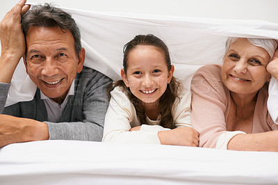 Buy stock photo A smiling little girl spending time with her grandparents