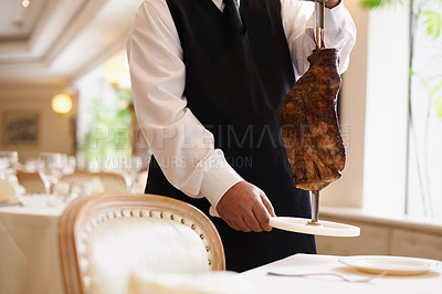 Buy stock photo Cropped image of a male waiter holding a skewer with a large piece of meat on it