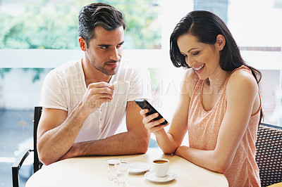 Buy stock photo Shot of a young woman using her mobile phone during a coffee date