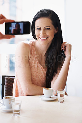 Buy stock photo Shot of a woman having her picture taken with a phone at a cafe