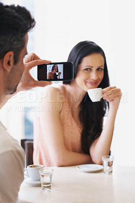 Buy stock photo Shot of a man taking a snapshot of his wife with his phone at a cafe
