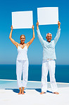 Senior couple at the beach holding a billboard