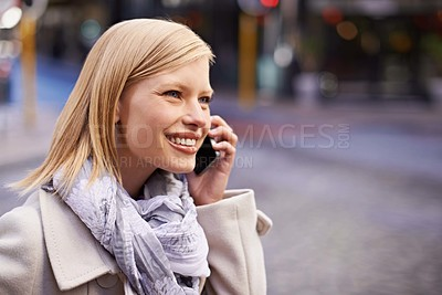 Buy stock photo Cropped shot of a young woman talking on her cellphone in the street