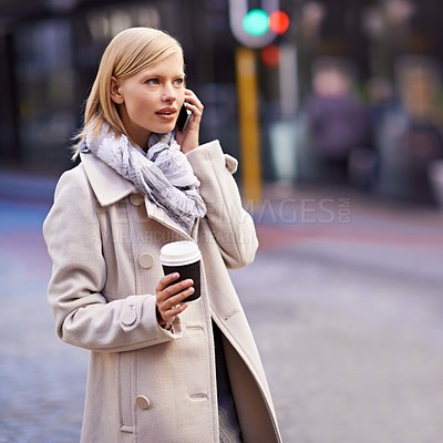 Buy stock photo Cropped shot of a young woman talking on her cellphone while walking in the street with a coffee