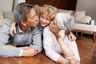 Buy stock photo A young boy lying down and smiling with his grandparents