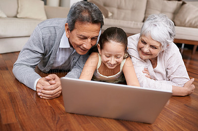 Buy stock photo A young girl and her grandparents lying on the floor and looking at a laptop
