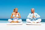 Healthy senior couple meditating at the sea shore