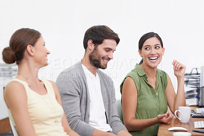 Buy stock photo Shot of three work colleagues enjoying a conversation in the office