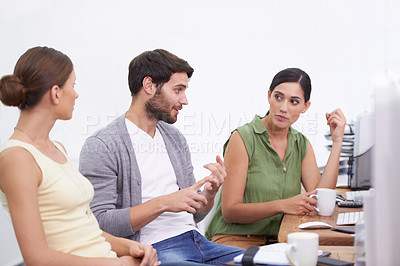 Buy stock photo Shot of a young businessman explaining something to his colleagues