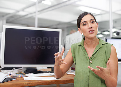 Buy stock photo Shot of a young businesswoman explaining something at her desk