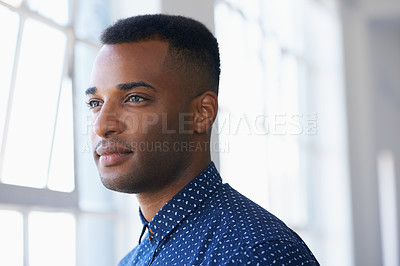 Buy stock photo Profile of a young ethnic man looking thoughtfully out of a window