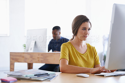 Buy stock photo A young woman working at her desk with her colleague in the background