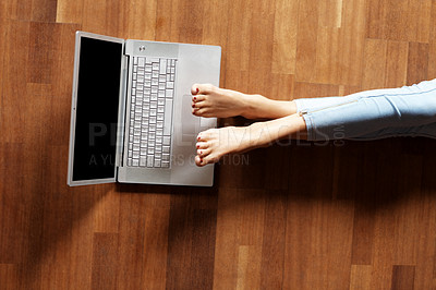 Buy stock photo Legs of a young woman lying on the floor with lapt