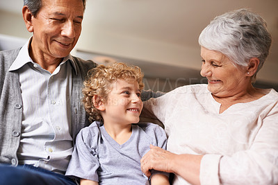 Buy stock photo Shot of a little boy sitting with his grandparents at home