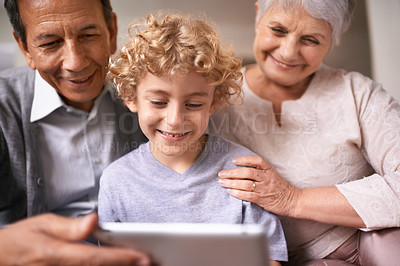 Buy stock photo A little boy using a tablet while sitting with his grandparents