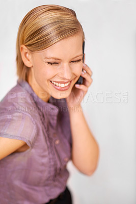 Buy stock photo Shot of a beautiful smiling young woman talking on a cellphone