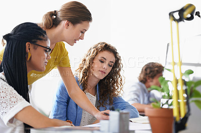 Buy stock photo Shot of a group of young coworkers talking at a desk