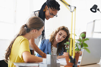 Buy stock photo Shot of young female coworkers talking over a computer