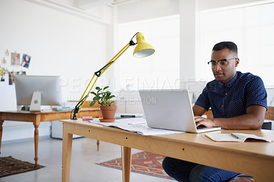 Buy stock photo A handsome young man working at his desk