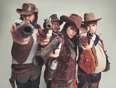 Buy stock photo A band of outlaws standing isolated on gray while pointing their pistols at you