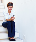 Pretty business woman with mobile on the stairs