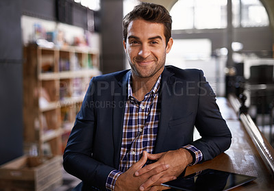 Buy stock photo Shot of a young man sitting in a coffee shop