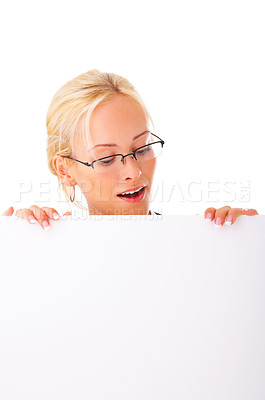 Buy stock photo Studio shot of a young woman standing behind a blank sign isolated on white