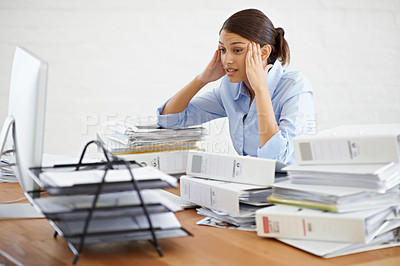 Buy stock photo A young businesswoman looking overwhelmed while surrounded by paperwork