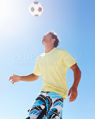 Buy stock photo A young teenage guy heading a football against a bright blue sky - copyspace