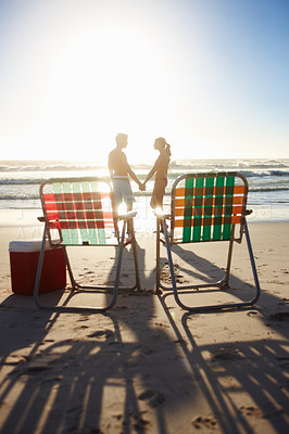 Buy stock photo Romantic young couple at the beach during sunset