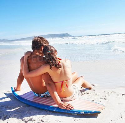 Buy stock photo Loving couple sitting on a surf board at the beach looking out at the waves - copyspace