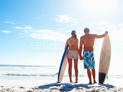 Buy stock photo Rear view of a couple holding surf boards at the sea shore