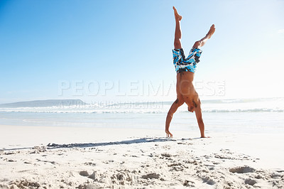 Buy stock photo Strong masculine guy doing handstand on the beach