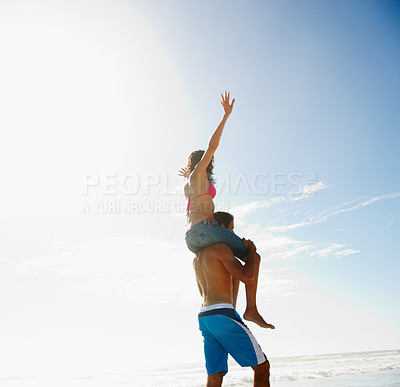 Buy stock photo Rear view of a guy carrying a friend on the shoulder at the sea shore
