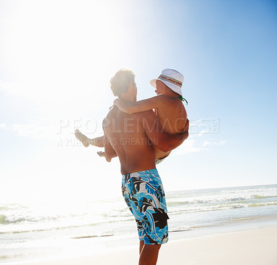 Buy stock photo Young man carrying girlfriend in his arms at the sea shore