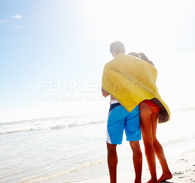 Buy stock photo Rear view of a young couple with a towel around them at the beach