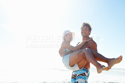 Buy stock photo Portrait of a handsome young man carrying his girlfriend in his arms at the beach