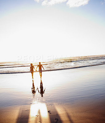 Buy stock photo Silhouette image of a beautiful couple running by the sea shore