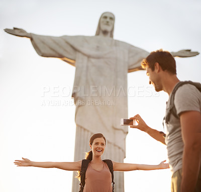Buy stock photo Shot of a happy young couple taking photos at the Christ the Redeemer statue