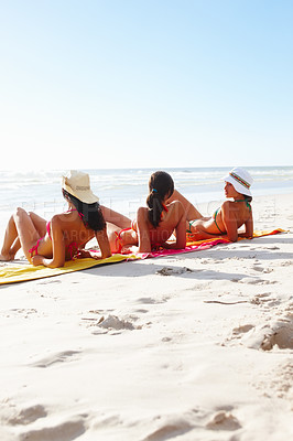 Buy stock photo Group of friends sunbathing together at the beach