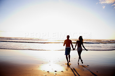 Buy stock photo Rear view portrait of a young couple holding hands by the sea shore