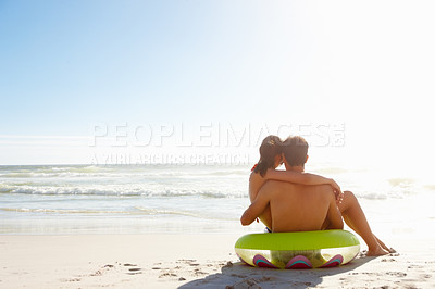 Buy stock photo An affectionate young couple relaxing on the beach