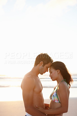 Buy stock photo Portrait of a young couple passionately holding eachother at the sea shore