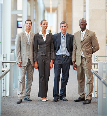 Buy stock photo Portrait of a happy business team standing together at a hallway