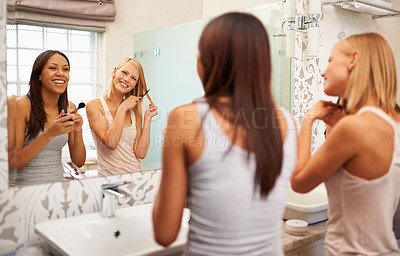 Buy stock photo Shot of two young woman applying makeup and styling their hair in front of a mirror