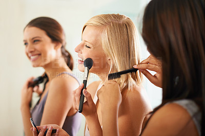 Buy stock photo Shot of three friends applying makeup and styling their hair together