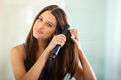 Buy stock photo Portrait of an attractive woman straightening her hair with a flat iron