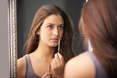Buy stock photo Shot of a young woman putting on lipgloss in front of the mirror